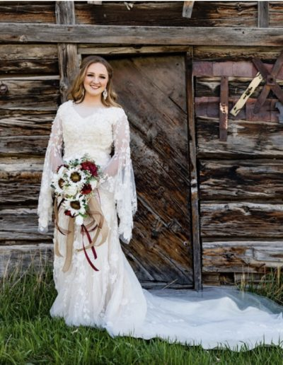 a woman in a wedding dress standing in front of an old, wooden cabin
