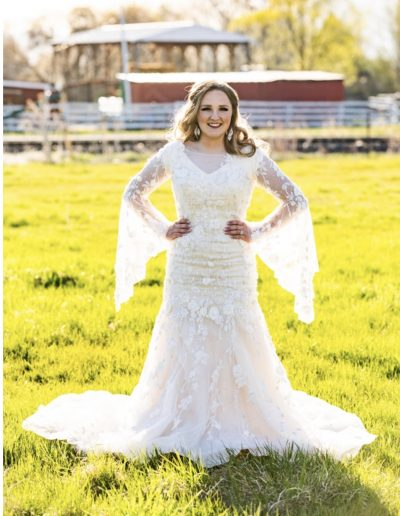 a woman in a wedding dress standing in a field with her hands on her hips