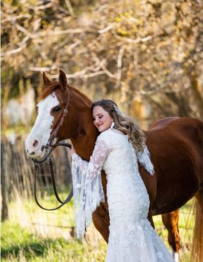 a woman in a wedding dress hugging a horse