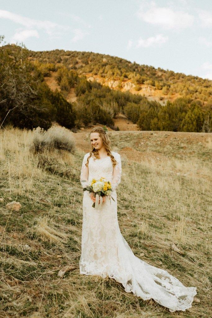 a beautiful bride with a boquet of flowers and a mountain in the background