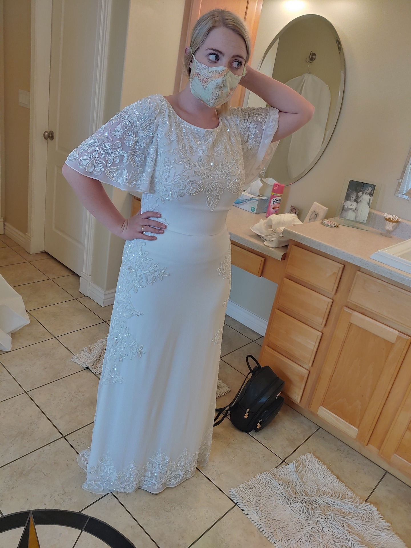 a woman in her wedding dress after hemming it from the waist, using the spare lace as a mask