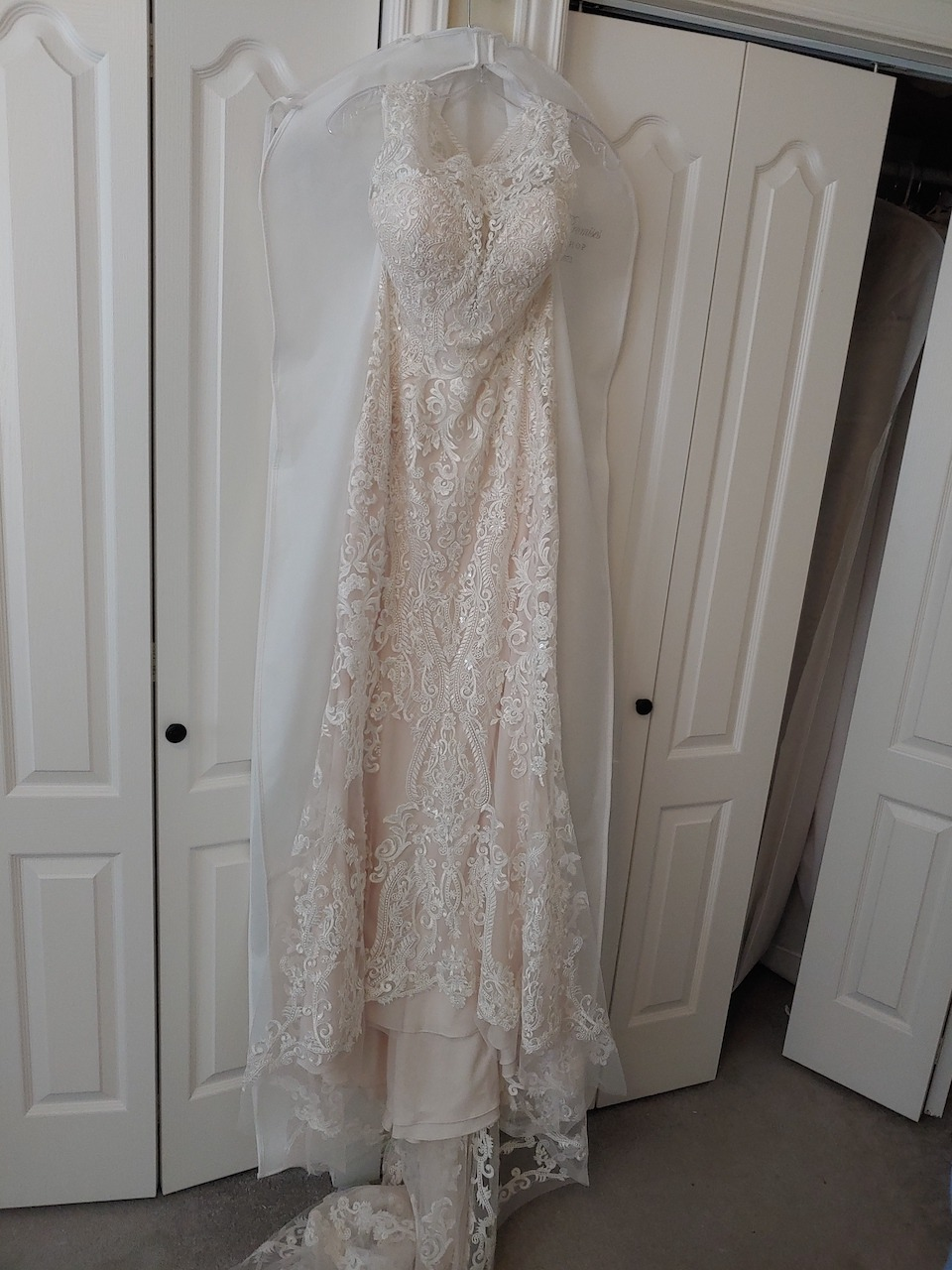 a wedding dress hanging up near a closet featuring a lace hem with netting border